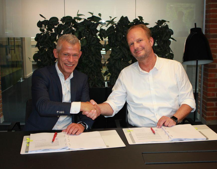 Søren Harding fra Altibox og Henrik Møller Nielsen fra OpenNet giver håndslag på den nye aftale
