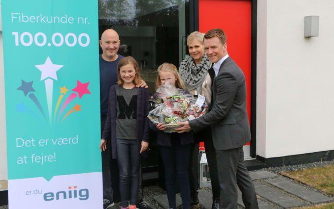 Familien Thrane (fra venstre: Ulrik, Sascha, Silke og Mirja) får overrakt en gavekurv af Eniigs fiberdirektør, Søren Lindgaard (th.)